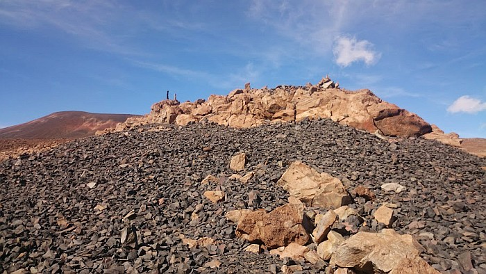 A prehistoric shrine with upright stones set in the lava rock, located above the quarry. The grey stones are all flakes and half-worked adzes, residues of 600 years of adze production.