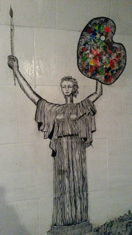 Street art of Rodina Mat (The Motherland Monument) holding a brush and a palette instead of a sword and a shield on a subway bridge at YevroMeydan