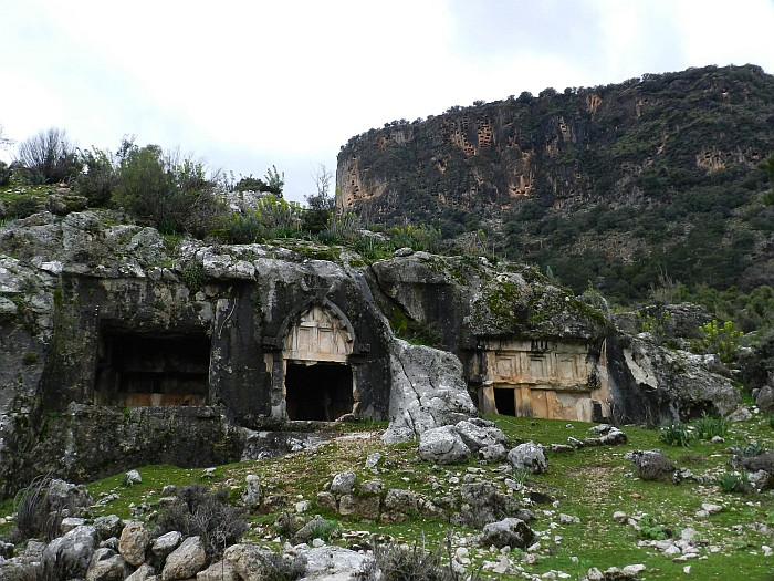 Bull-headed tomb in the front and rock tombs back on the mountain that look like pigeon-holes from far distance.