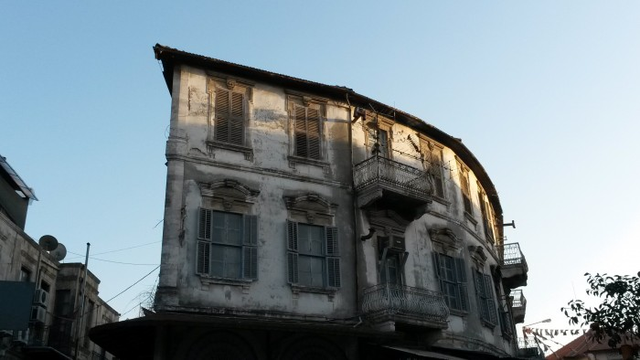 an old building trying to survive among urban restructuring that spreads all around the city.
